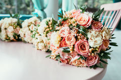Ramalhetes do casamento da noiva e das damas de honra na tabela antes do ceremo Imagem de Stock Royalty Free