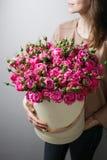 Ramalhetes luxuosos das flores na caixa do chapéu rosas nas mulheres das mãos Peônias cor-de-rosa da cor Fotografia de Stock Royalty Free