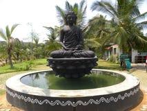 Ramanagara, Karnataka, Índia - 1º de janeiro de 2009 estátua preta da pedra da cor de Lord Buddha na meditação Foto de Stock