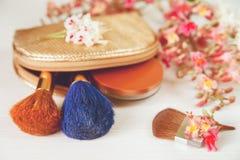 Ramas allí blancas y rosadas del árbol de castaña, polvo de bronce; Dos componen a Brown y los cepillos azules en el bolso cosmét Fotos de archivo libres de regalías