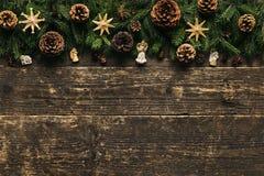 Ramas de árbol de abeto con los conos del pino, las chucherías de Navidad y las decoraciones en el fondo de madera, concepto fest Imagen de archivo