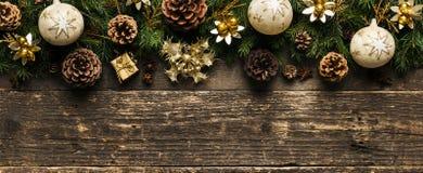 Ramas de árbol de abeto con los conos del pino, las chucherías de Navidad y las decoraciones en el fondo de madera, concepto fest Fotos de archivo
