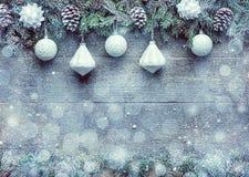 Ramas de árbol de abeto con los conos del pino y chucherías de Navidad en el fondo de madera, bandera festiva con el espacio de l Imagen de archivo