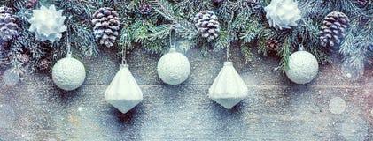 Ramas de árbol de abeto con los conos del pino y chucherías de Navidad en el fondo de madera, bandera festiva con el espacio de l Imágenes de archivo libres de regalías
