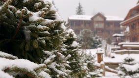 Ramas de árbol de abeto de la nieve que caen, cabañas de madera en fondo Nevadas pesadas en la estación de esquí del pueblo de mo almacen de video