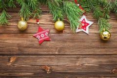 Ramas de árbol de abeto de la Navidad con las estrellas y la bola de madera de la Navidad Imagenes de archivo