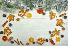 Ramas de árbol de navidad en nieve y galletas festivas con las especias Imágenes de archivo libres de regalías