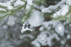 Ramas de árbol festivas de pino con el ornamento del reno y las chucherías brillantes de la Navidad en el fondo de madera Fotografía de archivo