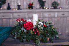 Ramas de árbol de navidad decorativas con la vela y rosas en la cesta Fotos de archivo libres de regalías
