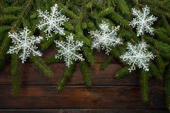 Ramas de árbol de navidad verdes en un fondo de madera oscuro Fondo del Año Nuevo con los copos de nieve blancos Visión superior Fotografía de archivo libre de regalías
