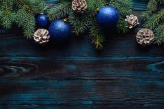 Ramas de árbol de pino de las decoraciones del Año Nuevo y de la Navidad, conos, juguetes azules de la Navidad en un fondo de mad Fotos de archivo libres de regalías