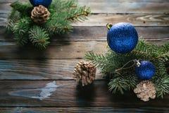 Ramas de árbol de pino de las decoraciones del Año Nuevo y de la Navidad, conos, juguetes azules de la Navidad en un fondo de mad Fotografía de archivo
