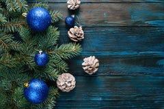 Ramas de árbol de pino de las decoraciones del Año Nuevo y de la Navidad, conos, juguetes azules de la Navidad en un fondo de mad Foto de archivo libre de regalías