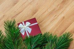 Ramas de la caja y del pino de regalo en fondo de madera Fotografía de archivo libre de regalías