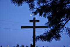 Ramas de la cruz y del pino en el primero plano y la luna en el fondo fotografía de archivo libre de regalías