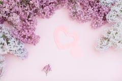 Ramas de la lila y dos corazón rosado en un espacio vacío del fondo rosa claro para su texto, visión superior Un corazón grande y Imágenes de archivo libres de regalías