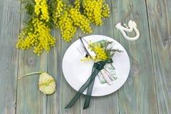 Ramas de la loza y de la mimosa en una tabla imagen de archivo libre de regalías