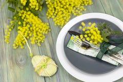 Ramas de la loza y de la mimosa en una tabla de madera fotografía de archivo