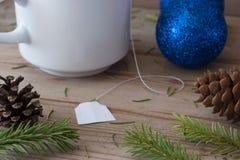 Ramas de las decoraciones, de árbol de navidad y taza de té Foto de archivo