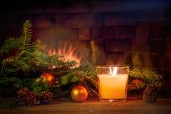 Ramas de un árbol de navidad, decoraciones, una vela en una tabla de madera delante de la chimenea A?o Nuevo o la Navidad fotos de archivo