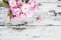 Ramas del árbol frutal en flores rosados en florero en la tabla de madera Imágenes de archivo libres de regalías