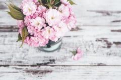 Ramas del árbol frutal en flores rosados en florero en la tabla de madera Imagen de archivo