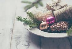 Ramas del abeto y juguetes de la Navidad en la placa Fotos de archivo