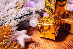 Ramas Spruce en la decoración del oro de la nieve y de la Navidad blanca en fondo de madera Foto de archivo libre de regalías