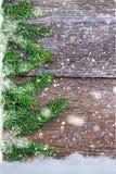Ramas Spruce en los tableros de madera con los copos de nieve Fotografía de archivo