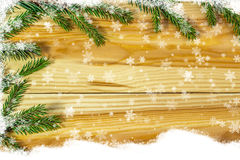 Ramas Spruce en los tableros de madera con los copos de nieve Foto de archivo libre de regalías