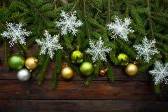 Ramas spruce vivas verdes en un fondo de madera oscuro Fondo del Año Nuevo con las bolas hermosas y la nieve blanca Visión superi Foto de archivo
