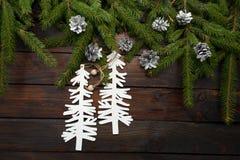 Ramas spruce vivas verdes en un fondo de madera oscuro Fondo del Año Nuevo con los conos y los árboles de navidad de la cartulina Fotografía de archivo libre de regalías