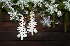 Ramas spruce vivas verdes en un fondo de madera oscuro Fondo del Año Nuevo con los conos y copos de nieve y cartulina blancos Cri Foto de archivo libre de regalías