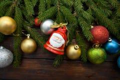 Ramas spruce vivas verdes en un fondo de madera oscuro Fondo del Año Nuevo con los globos y las campanas multicolores en la idea  Fotos de archivo libres de regalías