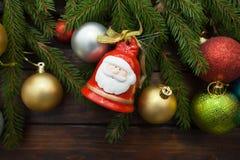 Ramas spruce vivas verdes en un fondo de madera oscuro Fondo del Año Nuevo con los globos y las campanas multicolores en la idea  Foto de archivo