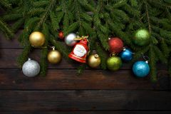 Ramas spruce vivas verdes en un fondo de madera oscuro Fondo del Año Nuevo con los globos y las campanas multicolores en la idea  Fotos de archivo