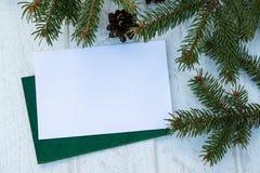 Ramas verdes de un árbol de navidad y de conos en un fondo del tablero blanco Visi?n superior con el espacio de la copia foto de archivo libre de regalías