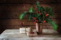 Ramas y escaramujos del abeto en un florero y un regalo de cerámica de la Navidad Fotografía de archivo