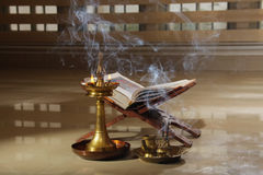 Ramayana on stand with an Oil lamp. Stock Photos