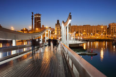 Rambla de Mar over Port Vell in Barcelona at Night. Rambla de Mar wooden walkway over Port Vell in the city of Barcelona at night in Catalonia, Spain Royalty Free Stock Images