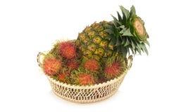 Rambutan Ananas im Korbholz Lokalisiert auf weißem backgroun Stockfoto