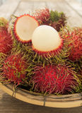 Rambutan. Asian fruit in basket on wooden table Royalty Free Stock Image