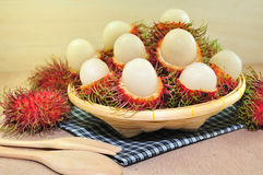 Rambutan. In Bamboo Basket on Wooden Background Royalty Free Stock Photography