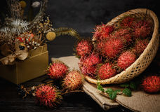 Rambutan in a bamboo basket on wooden table  on   black background. Rambutan in a bamboo basket on wooden table  on black background Royalty Free Stock Image