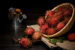 Rambutan in a bamboo basket on wooden table  on   black background. Rambutan in a bamboo basket on wooden table  on black background Royalty Free Stock Images