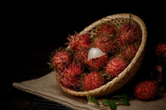 Rambutan in a bamboo basket on wooden table isolated on   black background Stock Photos