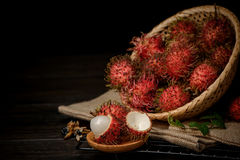 Rambutan in a bamboo basket on wooden table isolated on   black background. Rambutan in a bamboo basket on wooden table isolated on black background Royalty Free Stock Photo