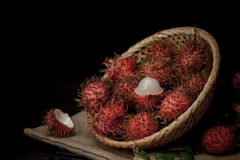 Rambutan in a bamboo basket on wooden table isolated on   black background. Rambutan in a bamboo basket on wooden table isolated on black background Royalty Free Stock Photography