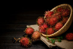 Rambutan in a bamboo basket on wooden table isolated on   black background. Rambutan in a bamboo basket on wooden table isolated on black background Stock Image