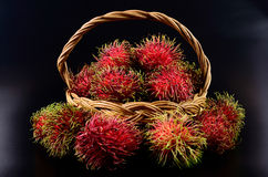 Rambutan in basket on black background. Rambutan in basket on a black background Stock Photo